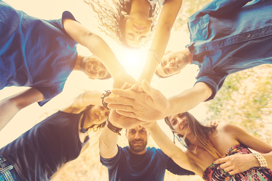 Multiracial group of friends stand together with hands on stack and looking down at camera. They are six persons, three boys and three girls, on their early twenties. Teamwork and cooperation concepts.