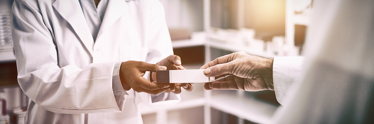 image of blurred out pharmacy with hands of pharmacist in white coats holding prescriptions